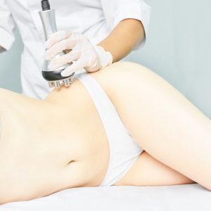 Perfect body radio treatment. Woman at spa procedure. Doctor hand and girl body. RF cosmetology lifting. Belly skin