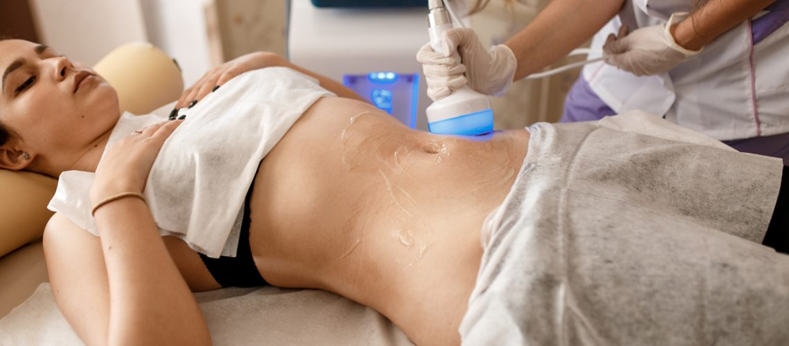 Hardware cosmetology. Body care. Spa treatment. Ultrasound cavitation body contouring treatment. Woman getting anti-cellulite and anti-fat therapy in beauty salon
