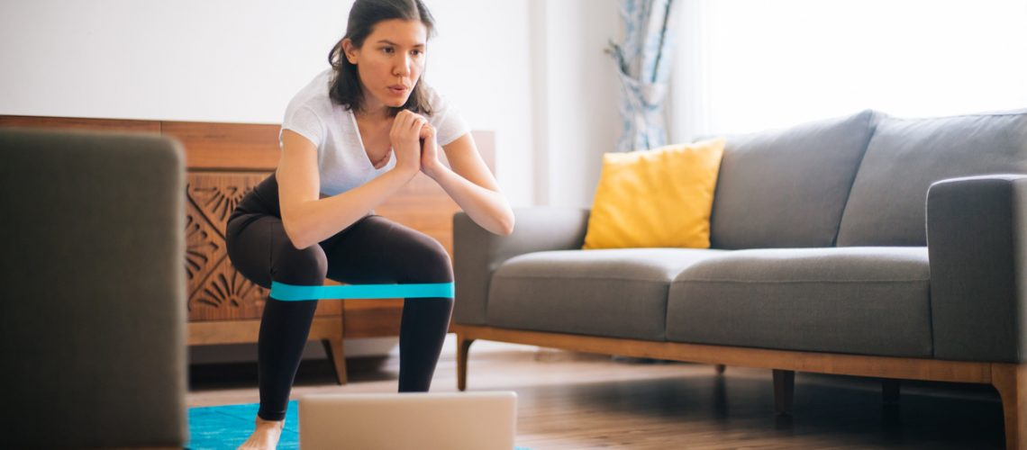 Sporty young woman exercising at home with resistance band
